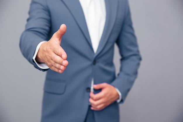Nahaufnahmeporträt eines geschäftsmannes, der hand für handschlag über graue wand streckt