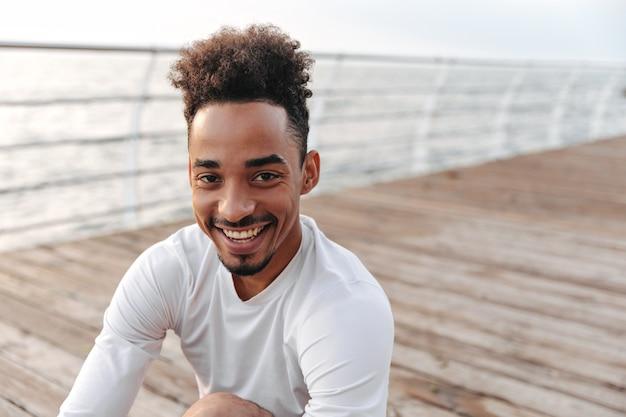 Nahaufnahmeporträt eines glücklichen jungen dunkelhäutigen mannes in weißem sport-langarm-t-shirt, das aufrichtig in der nähe von meer lächelt