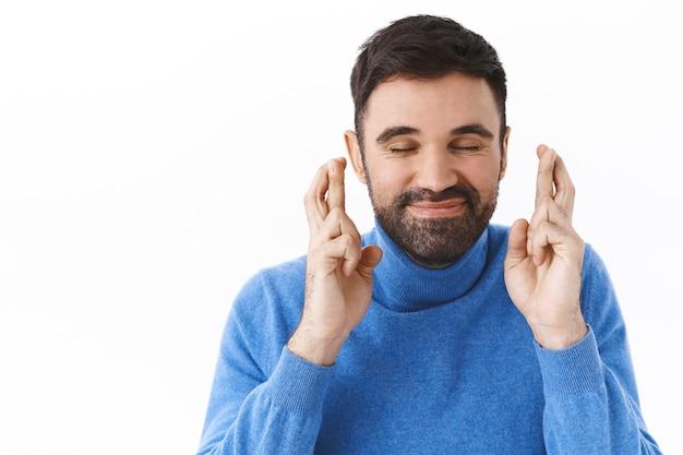 Nahaufnahmeporträt eines glücklichen, verträumten kaukasischen bärtigen mannes, enge augen und optimistisches lächeln als kreuzfinger viel glück, wünsche machend, wunder ankündigen oder träume wahr werden lassen, weiße wand