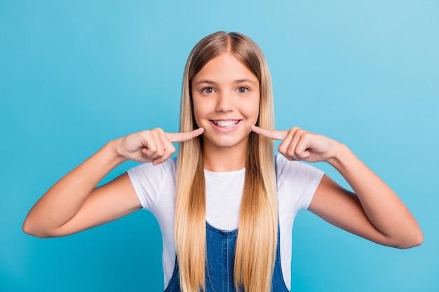 Nahaufnahmeporträt eines gut aussehenden, fröhlichen blonden mädchens, das den zahnaufhellungseffekt einzeln auf pastellblauem hintergrund zeigt