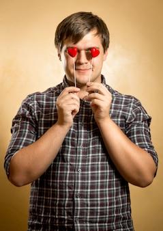 Nahaufnahmeporträt eines gutaussehenden mannes mit roten herzen anstelle der augen
