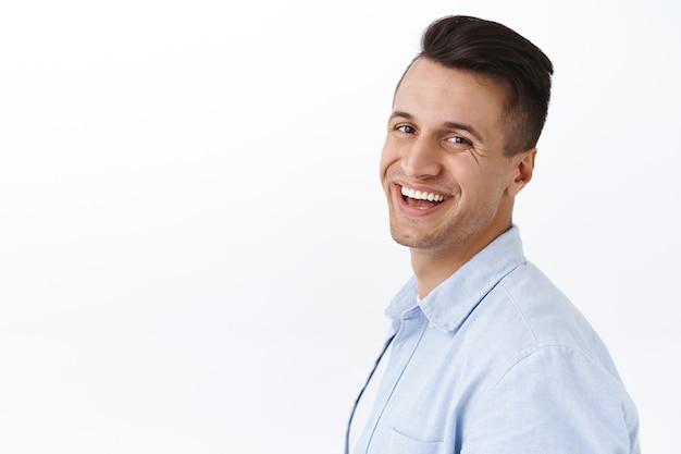 Nahaufnahmeporträt eines gutaussehenden, stilvollen jungen mannes, der im profil steht, den kopf mit strahlendem lächeln drehen, zufriedenheit und begeisterung ausdrücken, weiße wand erfreut
