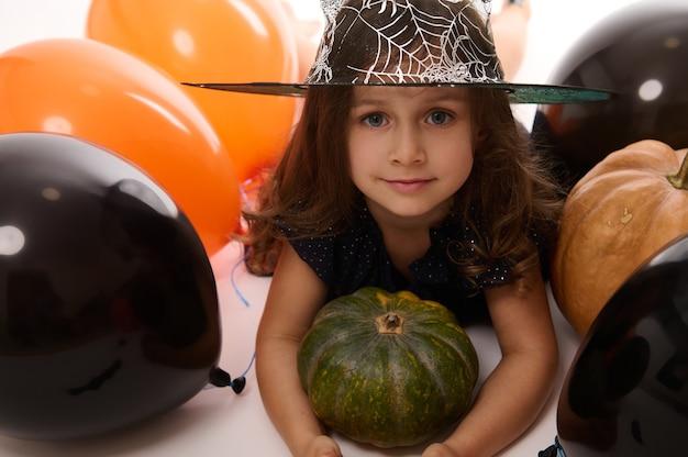 Nahaufnahmeporträt eines hübschen kleinen mädchens in karnevalshexenkostüm und zauberhut, das die kamera anschaut, die mit kürbis im weißen hintergrund mit farbigen schwarzen und orangefarbenen ballons posiert. halloween-konzept