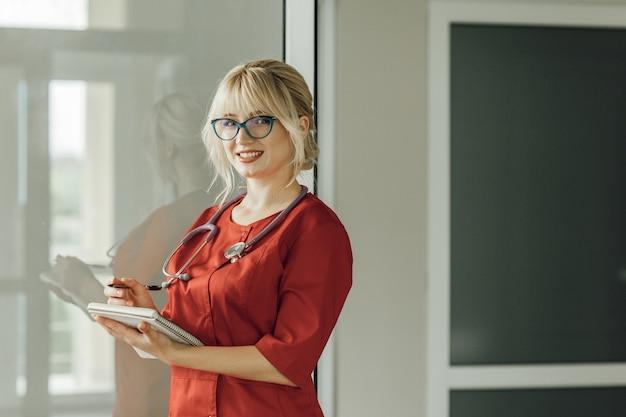 Nahaufnahmeporträt eines jungen blonden arztes in einer roten uniform mit einem stethoskop. ein arzt mit brille steht im krankenhaus, hält ein notizbuch mit einem stift in der hand und schaut in die kamera