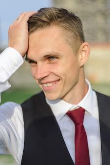 Nahaufnahmeporträt eines jungen bräutigams. ein mann glättet seine haare.