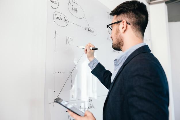 Nahaufnahmeporträt eines jungen dunkelhaarigen mannes in den gläsern mit laptop, der einen geschäftsplan auf whiteboard schreibt. er trägt ein blaues hemd und eine dunkle jacke. blick von der seite.