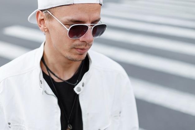 Nahaufnahmeporträt eines jungen hipster-mannes in einer modischen weißen jacke in einem schwarzen t-shirt in einer stilvollen baseballkappe in der runden sonnenbrille auf der straße