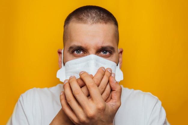 Nahaufnahmeporträt eines jungen mannes, der eine atemschutzmaske auf einem gelben husten in den händen trägt. atemwegserkrankung. symptome des coronavirus. grippeausbruch.