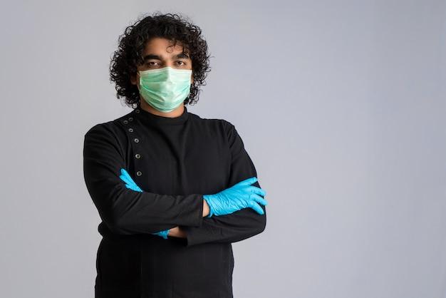 Nahaufnahmeporträt eines jungen mannes, der eine medizinische oder chirurgische maske trägt