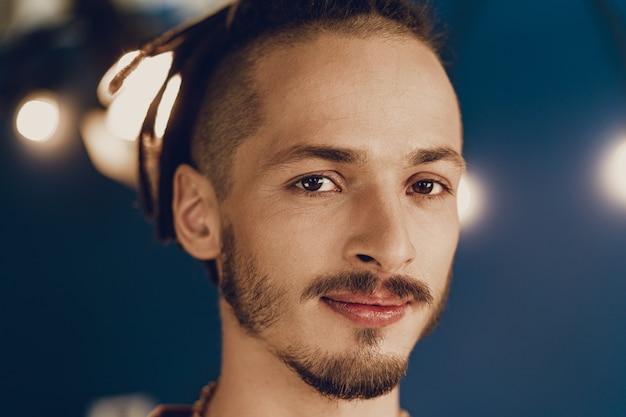 Nahaufnahmeporträt eines jungen stilvollen mannes mit dreadlocks-frisur
