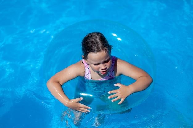Nahaufnahmeporträt eines kaukasischen mädchens, das einen aufblasbaren kreis angst vor dem schwimmen hält