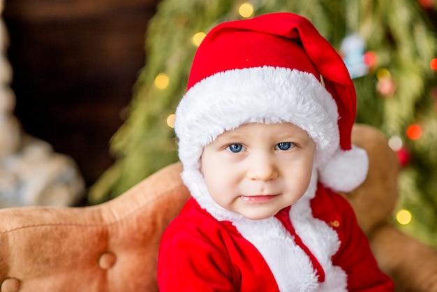 Nahaufnahmeporträt eines kleinen jungen als roter weihnachtsmann verkleidet