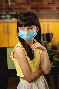 Nahaufnahmeporträt eines kleinen mädchens in einer schutzmaske steht in der küche.