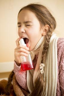 Nahaufnahmeporträt eines kranken mädchens im pullover mit halsspray throat