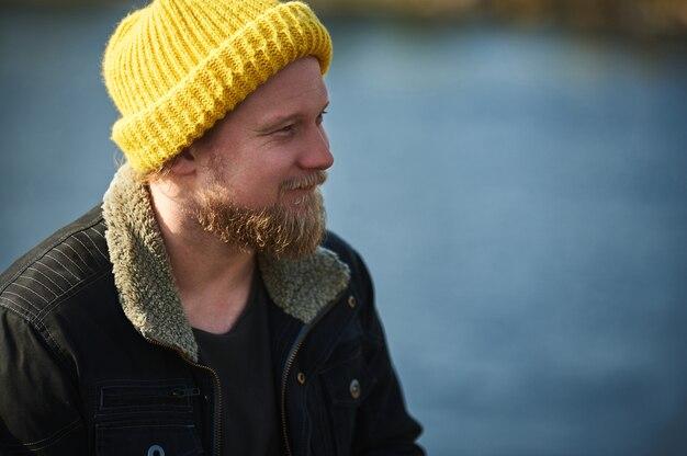 Nahaufnahmeporträt eines lächelnden ruhenden abenteurers im gelben hut am see