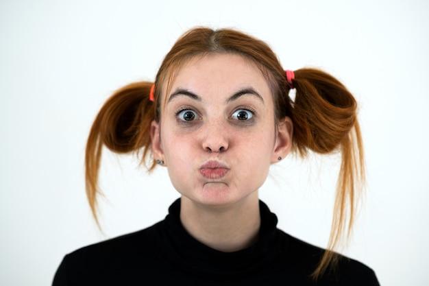 Nahaufnahmeporträt eines lustigen rothaarigen teenager-mädchens mit kindlicher frisur lokalisiert auf weißem hintergrund.