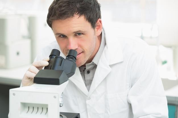 Nahaufnahmeporträt eines männlichen wissenschaftlichen forschers, der mikroskop im labor verwendet