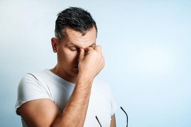 Nahaufnahmeporträt eines mannes, sein gesicht mit seinen händen bedeckend.