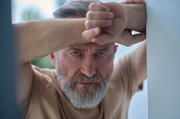 Nahaufnahmeporträt eines mürrischen einsamen grauhaarigen reifen mannes, der gegen die wand gelehnt und nach vorne starrt