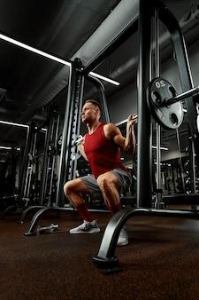Nahaufnahmeporträt eines muskulösen mannestrainings mit langhantel im fitnessstudio. brutaler bodybuilder athletischer mann mit sixpack, perfekten bauchmuskeln, schultern, bizeps, trizeps und brust.
