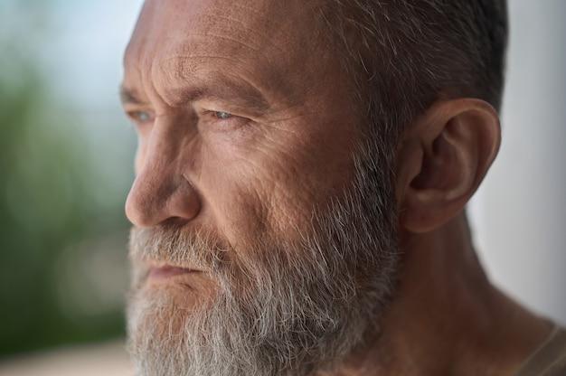 Nahaufnahmeporträt eines nachdenklichen traurigen mannes mit grauem bart und kurzen haaren, die wegschauen