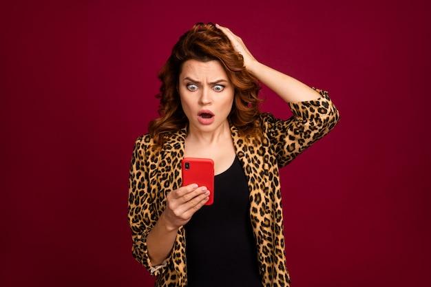 Nahaufnahmeporträt eines netten, attraktiven, hübschen, besorgten, erstaunten, gewellten mädchens mit gadget, das gefälschte nachrichten 5g durchsucht, einzeln auf rotem kastanienbraunem burgunder-marsala-farbhintergrund