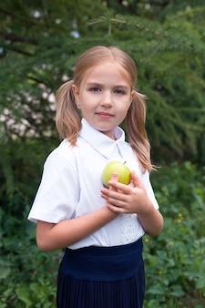 Nahaufnahmeporträt eines netten kleinen glücklichen mädchens in einer schuluniform, das einen apfel isst. schule. bildung.