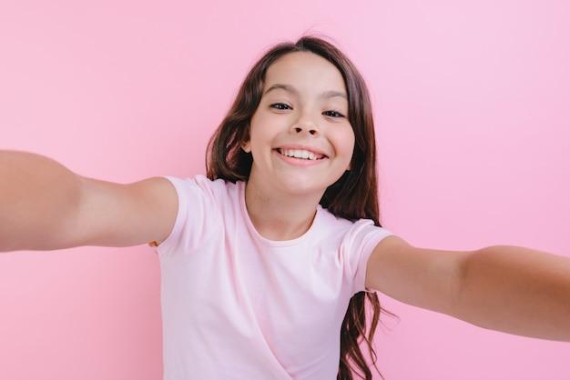 Nahaufnahmeporträt eines netten mädchens über rosa studiowith, das hände geraderichtet