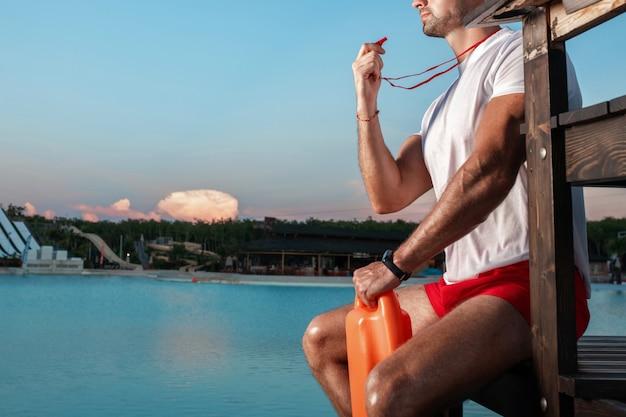 Nahaufnahmeporträt eines nicht erkennbaren rettungsschwimmers mit einer pfeife in seinen händen