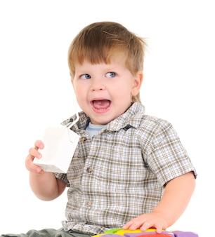 Nahaufnahmeporträt eines reizenden kleinen jungen, der fruchtsaft von einem strohhalm auf einer weißen wand trinkt. konzept von babynahrung und gesunder ernährung für kinder. copyspace
