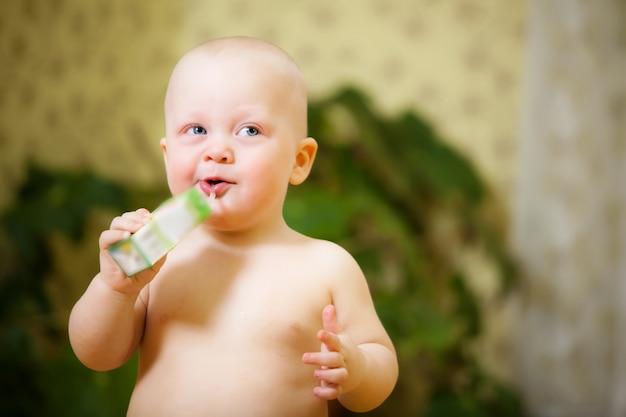 Nahaufnahmeporträt eines reizenden kleinen jungen, der fruchtsaft von einem strohhalm trinkt. konzept von babynahrung und gesunder ernährung für kinder.