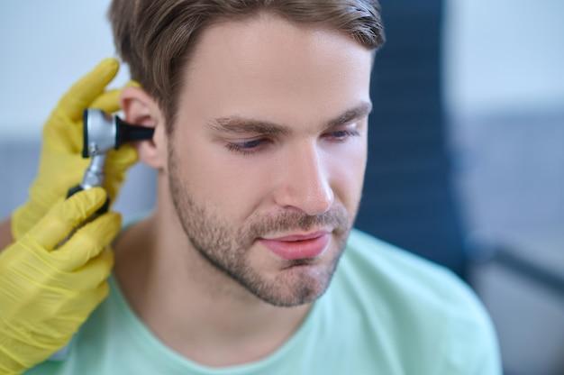 Nahaufnahmeporträt eines ruhigen, dunkelhaarigen, bärtigen, attraktiven jungen mannes, der sich einer ärztlichen untersuchung unterzieht, die von einer erfahrenen hno-ärztin durchgeführt wird