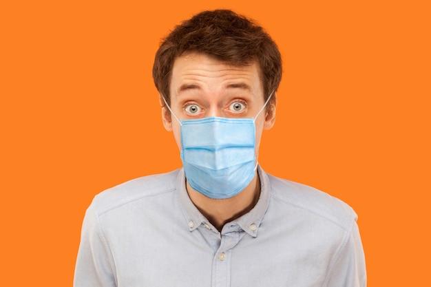 Nahaufnahmeporträt eines schockierten jungen arbeitermannes mit chirurgischer medizinischer maske, der mit großen augen die kamera steht und betrachtet. indoor-studioaufnahme auf orangem hintergrund isoliert.