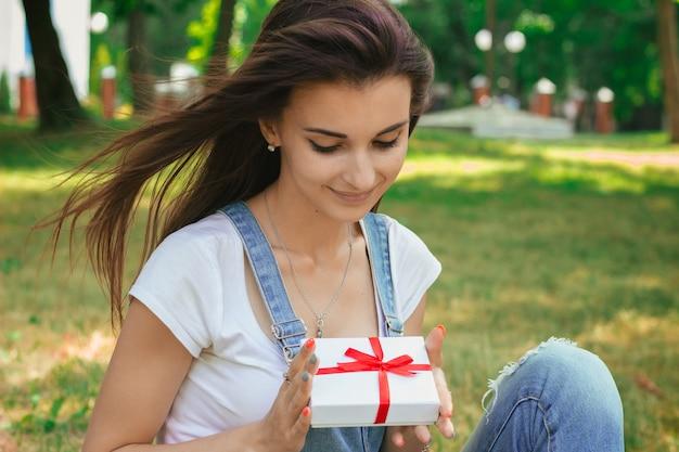 Nahaufnahmeporträt eines schönen brünetten teen mit einem geschenk in den händen im park