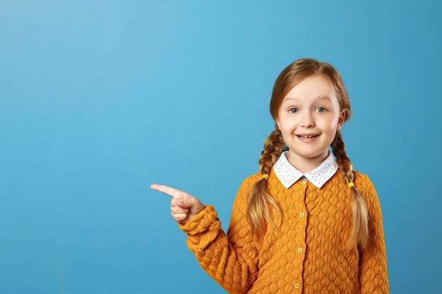 Nahaufnahmeporträt eines schulmädchens des kleinen mädchens auf einem blauen hintergrund