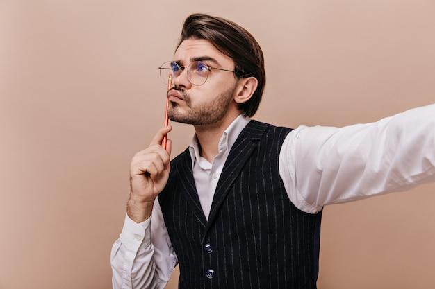 Nahaufnahmeporträt eines süßen jungen herrn in stilvoller brille, weißem hemd und gestreifter weste, der mit bleistift denkt und eine idee isoliert über beigefarbener wand schafft