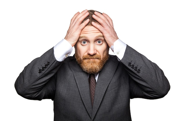 Nahaufnahmeporträt eines traurigen gutaussehenden geschäftsmannes mit gesichtsbart im schwarzen anzug, der seinen kopf hält und die kamera mit hoffnungslosem gesicht der trauer betrachtet. indoor-studioaufnahme isoliert auf weißem hintergrund.