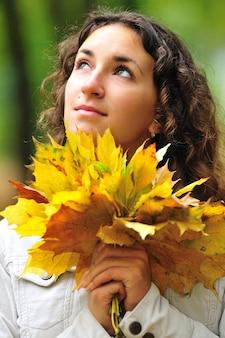 Nahaufnahmeporträt eines verträumten schönen jungen lockigen mädchens, das nach oben schaut und einen strauß gelber ahornblätter in ihren händen hält. das konzept des beginns der herbst- und studentenzeit