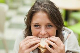 Nahaufnahmeporträt eines weiblichen studenten, der sandwich isst
