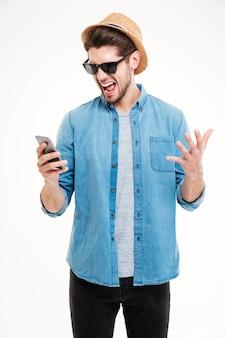 Nahaufnahmeporträt eines wütenden jungen mannes, der sein smartphone auf weißem hintergrund anschreit