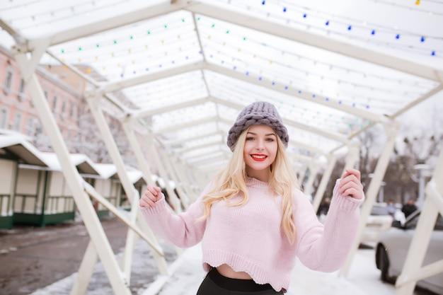 Nahaufnahmeporträt eines wunderbaren jungen modells mit hellem make-up, das eine trendige strickmütze und einen pullover trägt und im winter in der stadt posiert