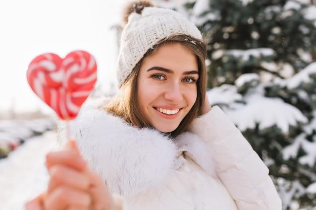 Nahaufnahmeporträt erstaunliche freudige lächelnde frau im sonnigen wintermorgen mit rosa lollypop auf straße. attraktive junge frau im weißen warmen wollhut, der kaltes wetter genießt. glückliche zeit, positive emotionen.