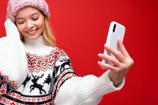 Nahaufnahmeporträt foto der ziemlich schüchternen positiven jungen blonden frau, die warmen strickmütze und winter trägt