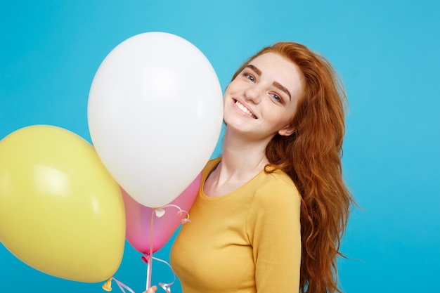 Nahaufnahmeporträt glückliches junges schönes attraktives rothaarmädchen, das mit bunter partyballonblau-pastellwand lächelt
