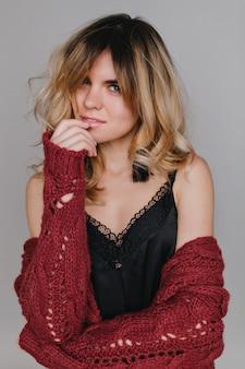 Nahaufnahmeporträt hübsche frau, die gesicht sinnlich berührt. , hat langes lockiges haar, rote lippen, stilvolle maniküre.