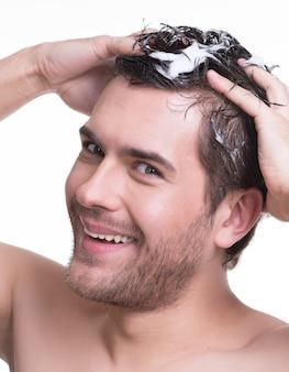 Nahaufnahmeporträt junger glücklicher lächelnder mann, der haare mit shampoo wäscht - lokalisiert auf weiß.