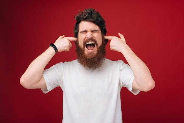 Nahaufnahmeporträt junger, wütender, unglücklicher, gestresster mann, der seine ohren bedeckt, isoliert auf roter wand. negative emotionen, gesichtsausdrücke.