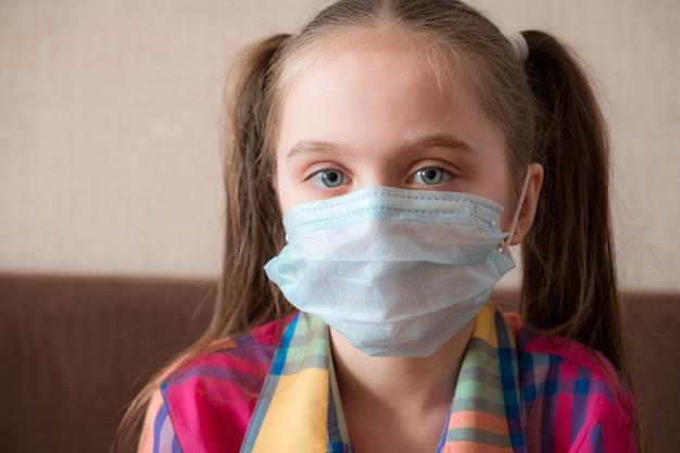 Nahaufnahmeporträt. konzept der coronavirus-quarantäne. kind, das medizinische gründungsgesichtsmaske während des grippevirus trägt und stoppgeste macht. covid-19 - selbstisolation zu hause.