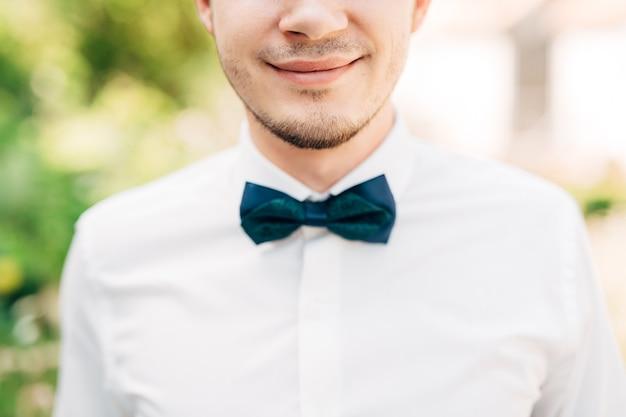 Nahaufnahmeporträt lächelnder bräutigam mit grüner fliege