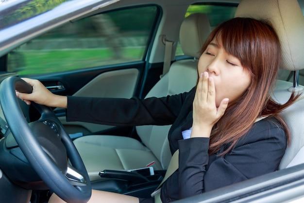 Nahaufnahmeporträt schläfrig, müde, nahe augen junge frau, die ihr auto nach langer stunde tri fährt